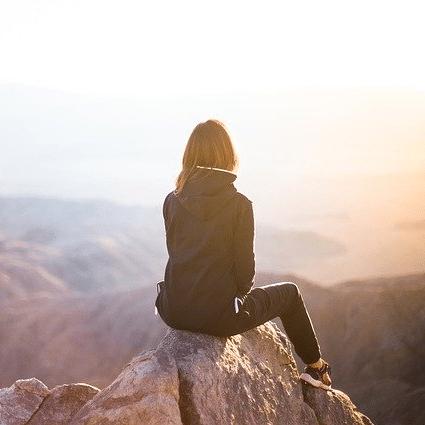 Mujer solo en la cima de una montaña