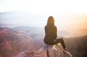 Mujer sola de espaldas en la cima de una montaña